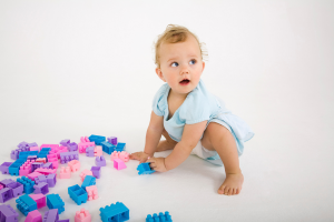 Baby baby squatting around pick purple and blue blocks while looking up