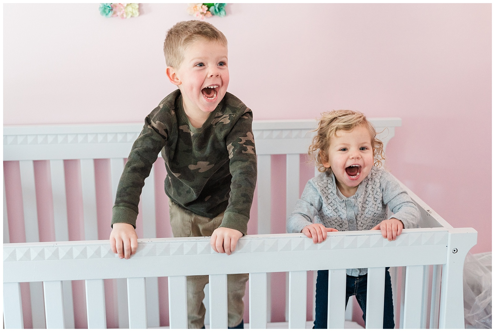 a young brother and sister jumping and laughing in the younger sister's crib