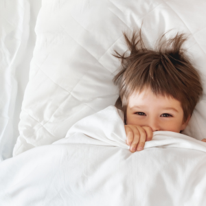 Toddler boy laying in a bed with the covers pull up to his face.