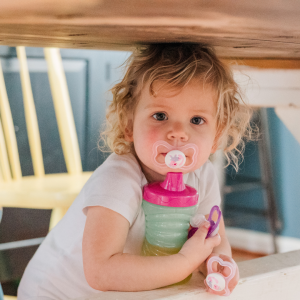 Baby girl standing under the kitchen table holding her juice cup and her 3 pacifiers.