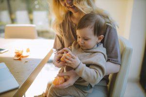 woman working with her toddler in her lap, sharing what she does with her child and creating a language rich environment for her baby